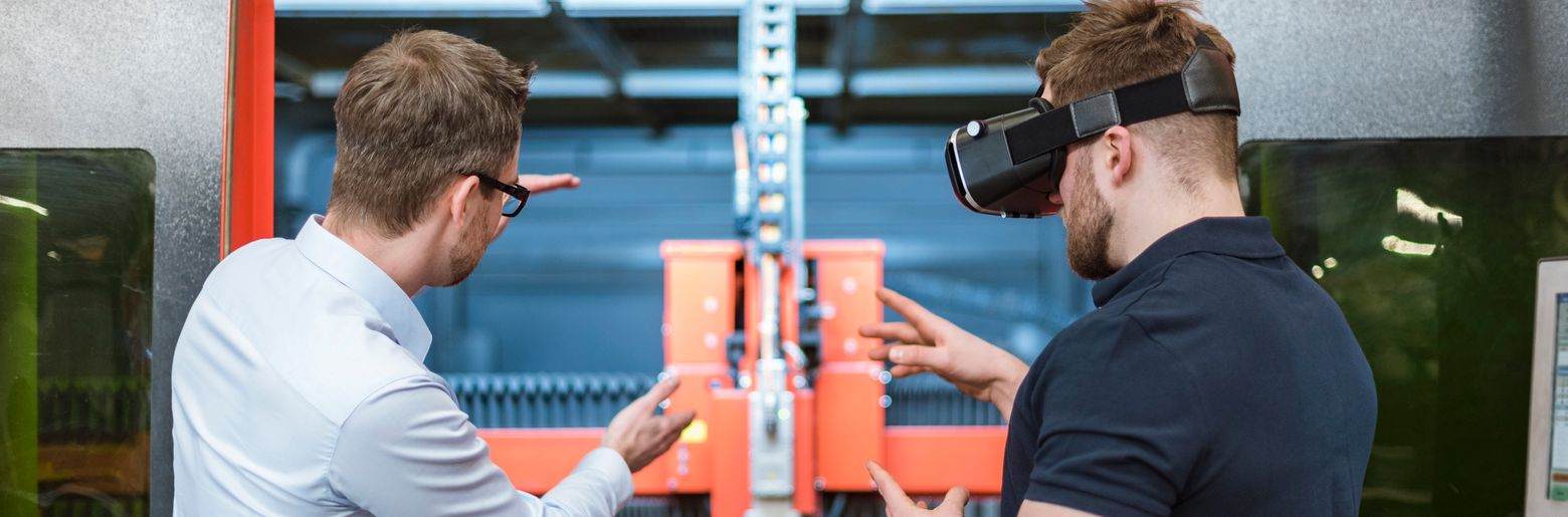 man explaining machine to colleague wearing vr